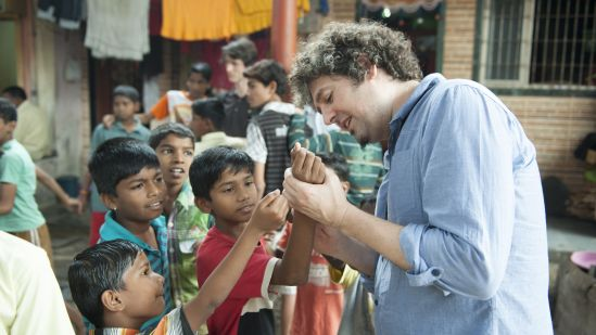 Luca Pattaroni (Professor at EPFL) reading palms to children in Bhandup.