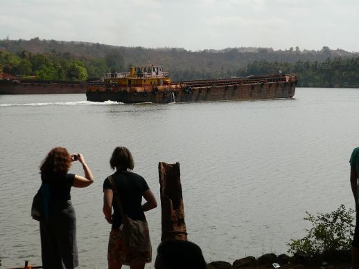 Two students of the Royal Institute of Arts taking pictures of a barge transporting Iron ore on the Mandovi river