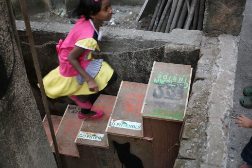 A girl climbs up a staircase built from plywood during the Khotachiwadi Imaginaries Workshop in January, 2016
