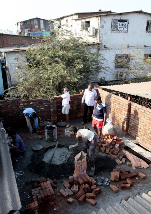 Masons laying bricks for a new space in Dharavi