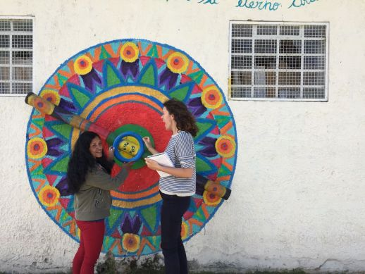 A resident explaining a Street Art installation produced during the last community art biennale to Paola