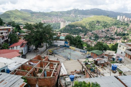 Overlooking the topography in Caracas with buildings under construction and a basketball court built by the community